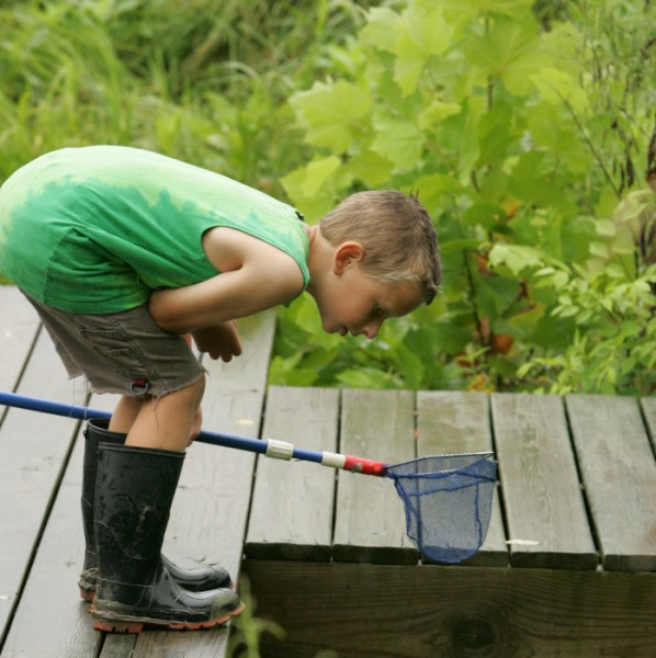 A boy enjoys looking for critters in the water at Big Muddy National Fish and Wildlife Refuge. Source: FWS.gov.